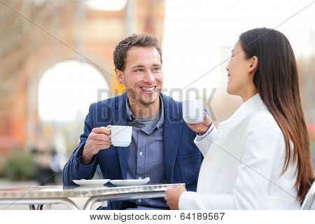 Couple dating drinking coffee at sidewalk cafe outdoors on date. Young beautiful professionals talking enjoying espresso laughing having in Barcelona, Spain near Arc de Triomf on Passeig de Sant Joan.