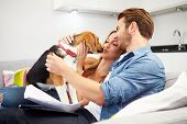 Couple Looking Through Personal Finances At Home With Dog poster