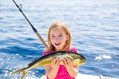 Blond kid girl fishing Dorado Mahi-mahi fish happy with trolling catch on boat deck poster