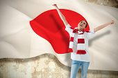Composite image of excited asian football fan cheering against japan flag poster