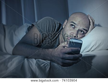 Young Cell Phone Addict Man Awake At Night In Bed Using Smartphone