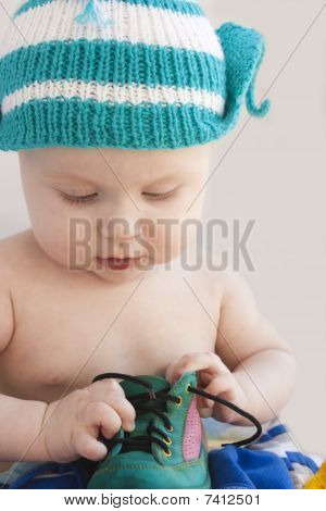 The Baby In A Cap Plays With A Green One Shoe