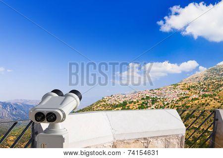 Binoculars and Arachova on mountain Parnassos, Greece - travel background