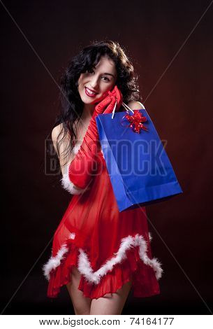 Sexy santa helper. Red dress and gloves. Carrying bag with gifts. Studio shot. Black background poster
