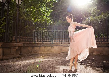 Young beautiful ballerina with pink dress dancing