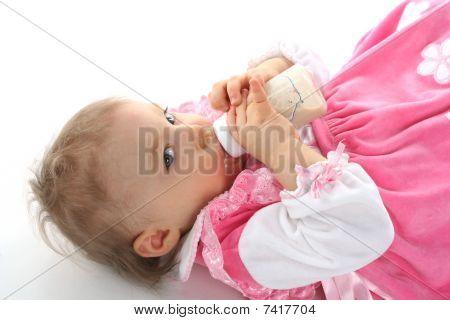 Pretty Baby Girl Is Drinking Milk In A Bottle