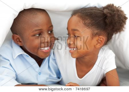 Portrait Of Laughing Siblings Lying Down On Bed
