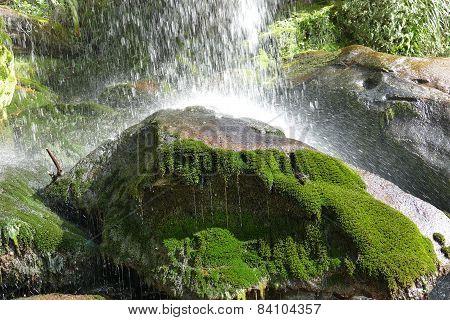 Splashing Water On A Green Mossy Rock
