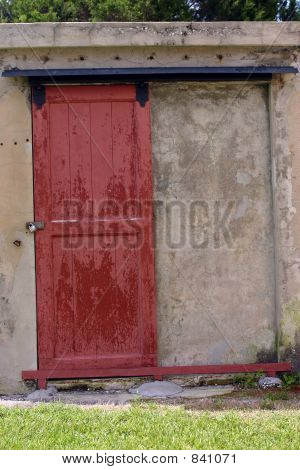 Weathered red door set in concrete wall