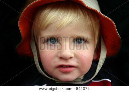 Portrait of blonde boy in orange and tan hat
