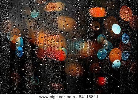Drops Of Rain On Glass With Defocused Lights. Abstract Background