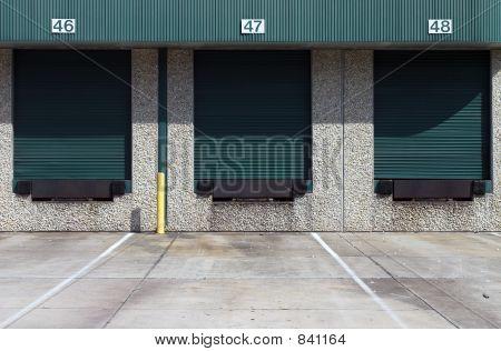 Three green warehouse loading bays