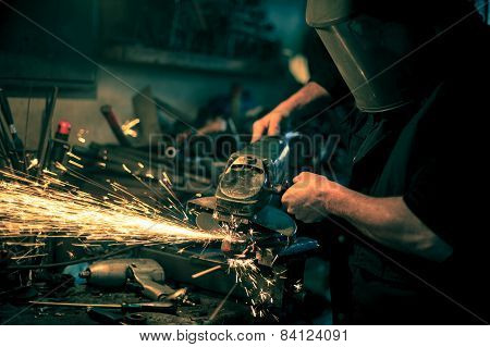Metal grinding on steel spare part in workshop poster