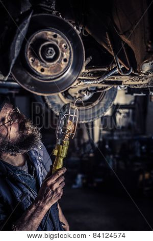 Mature Mechanic At Repair Service Station Inspecting Car Suspension