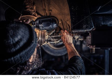 Mature Mechanic At Repair Service Station Inspecting Car Suspension