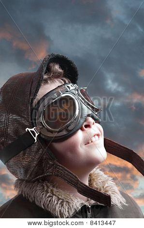 Boy Playing With Pilot´s Hat And Cloudy Background