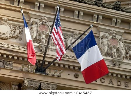 French and American Flags flying in front of European building facade poster