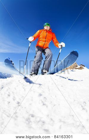 Active young man ready to skiing view from below