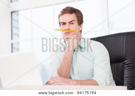 Young businessman making moustache with pencil