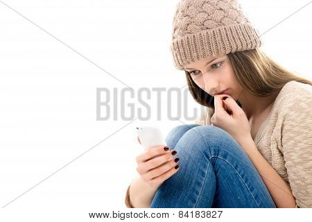 Upset Teenage Girl Looking At Her Smartphone