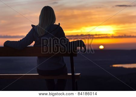 girl sitting on a banch at sunset