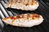 closeup of two grilled chicken breasts on a grill poster