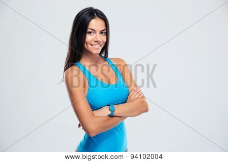 Happy fitness woman standing with arms folded over gray background and looking at camera