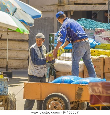 TAROUDANT, MOROCCO, APRIL 9, 2015: Local men unload boxes of dates from car