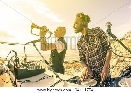 Trendy hipster dj playing summer hits at sunset beach party with trumpet jazz performer - Holidays vacation concept at open air club with house music groove location - Warm vintage sunshine filter poster