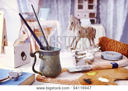Objects and tools of creative hobby, paintbrush, wooden horse on a table in vintage style,
