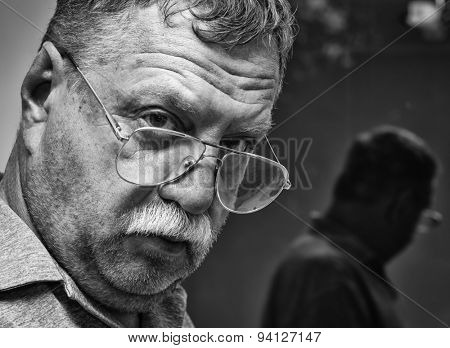 Portrait of a mature mustachioed man in glasses and his reflection in the window
