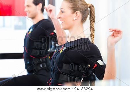 Female coach giving man and woman ems electro muscular stimulation exercise  poster