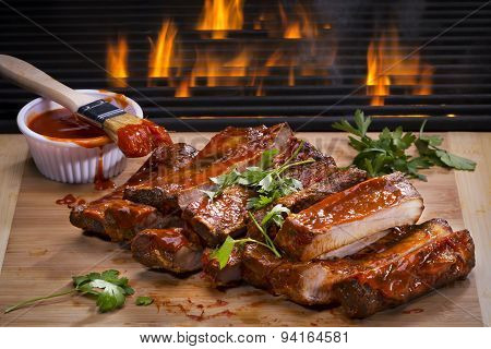 Barbecued Ribs next to a hot flaming grill