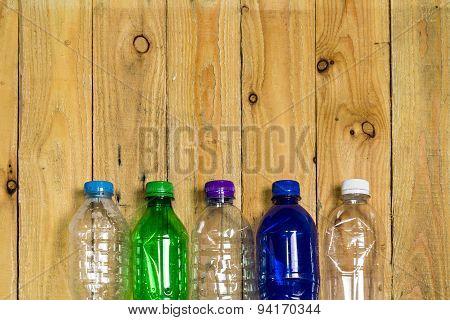 Used Plastic Bottles On Wooden Board