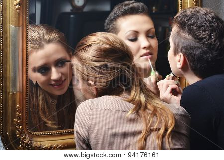 Beautiful Girls Having Fun While Putting Make Up In Front Of The Old Mirror