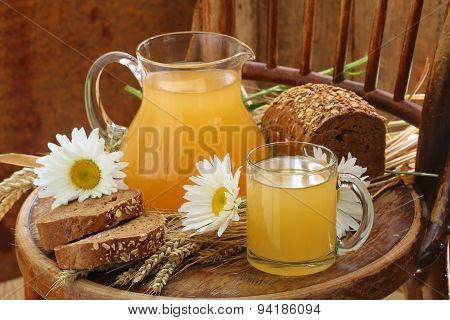 Kvass (Kvas) in a transparent mug a jug and rye bread poster