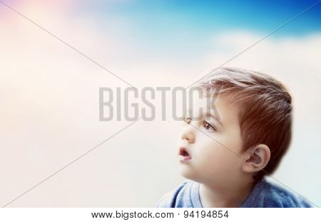 Boy looking at the sky with surprised expression. Imagination of a child poster