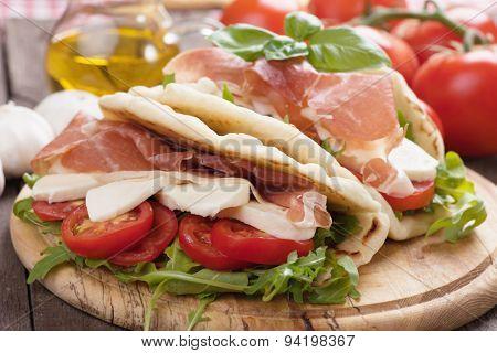 Piadina romagnola, italian flatbread sandwich with rocket salad, ricotta cheese and prosciutto