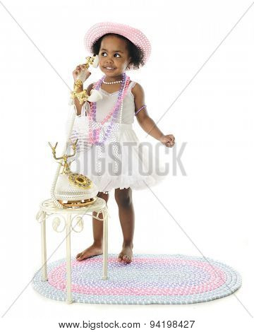An adorable two year old diva standing in her petticoat and pearls and chatting on a fancy French phone.  On a white background.
