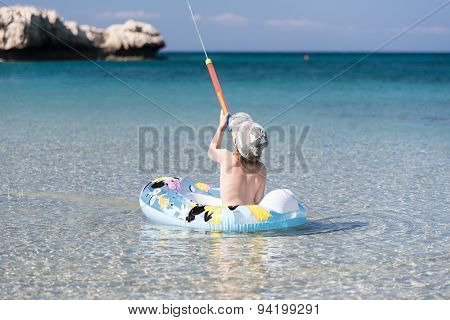Small Boy In Pontoon Shooting With Water Gun