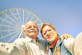 Happy retired senior couple taking selfie at travel around the world - Concept of active playful elderly with mobile phone - Mature people fun lifestyle in sunny day with strong sunlight color tones poster