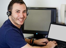 Young Call Center Agent Guy Smiling At The Camera