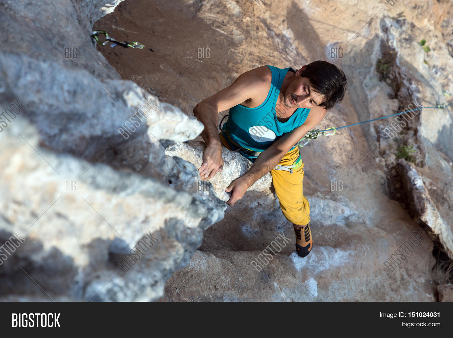 Top View of Mature Male Extreme Climber in bright sportive Clothing hanging  on unusual shaped Rock