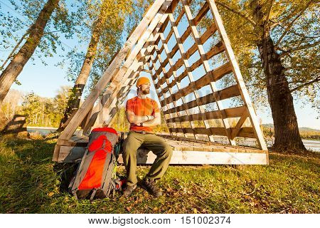 Young male with beard traveling, resting in the countryside sitting in hut of branches, with tourist rucksack while enjoying nature view and summer rest