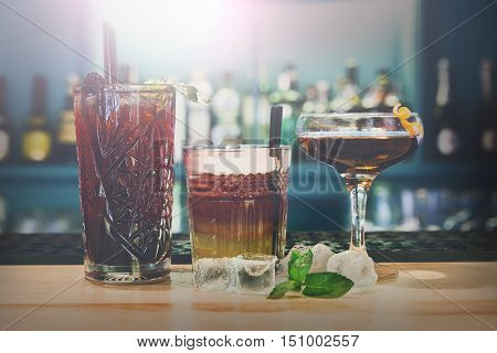 Closeup row of creative sweet exotic alcohol party cocktails in restaurant at bar background. Glasses with beverages on bar table, refreshing drinks with straws.