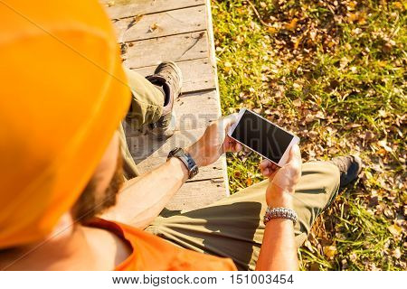 Young male traveling, resting in countryside sitting in hut of branches, with tourist rucksack, using smartphone while enjoying nature view and summer rest