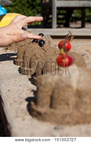 Final touch. Child making sand cakes in autumn season.