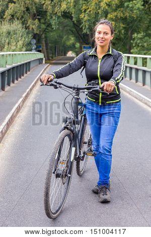 European woman standing with ATB mountainbike on bridge