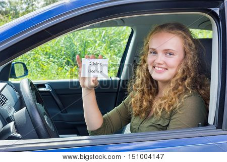 Young european woman showing card driving license in car