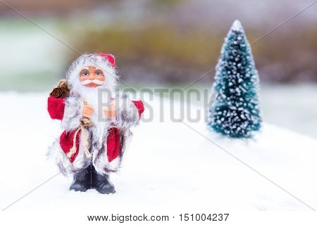 Santa Claus figurine standing in white snow outside